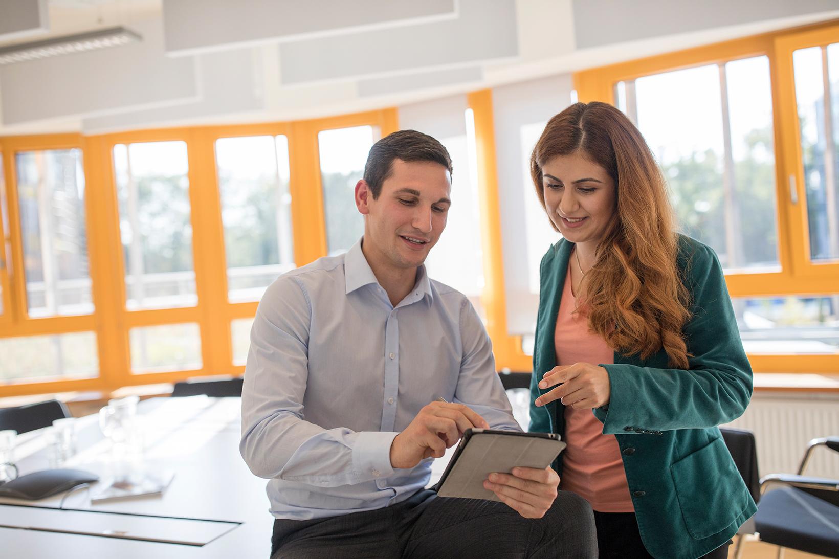 Mann und Frau über ein Tablet gebeugt