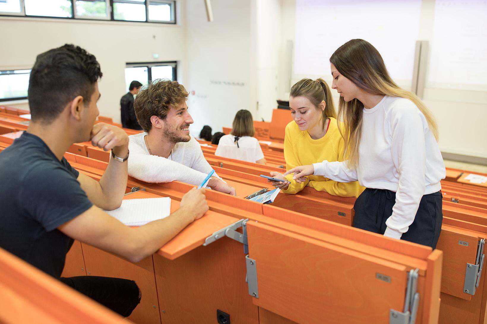Studierend unterhalten sich in einem Hörsaal
