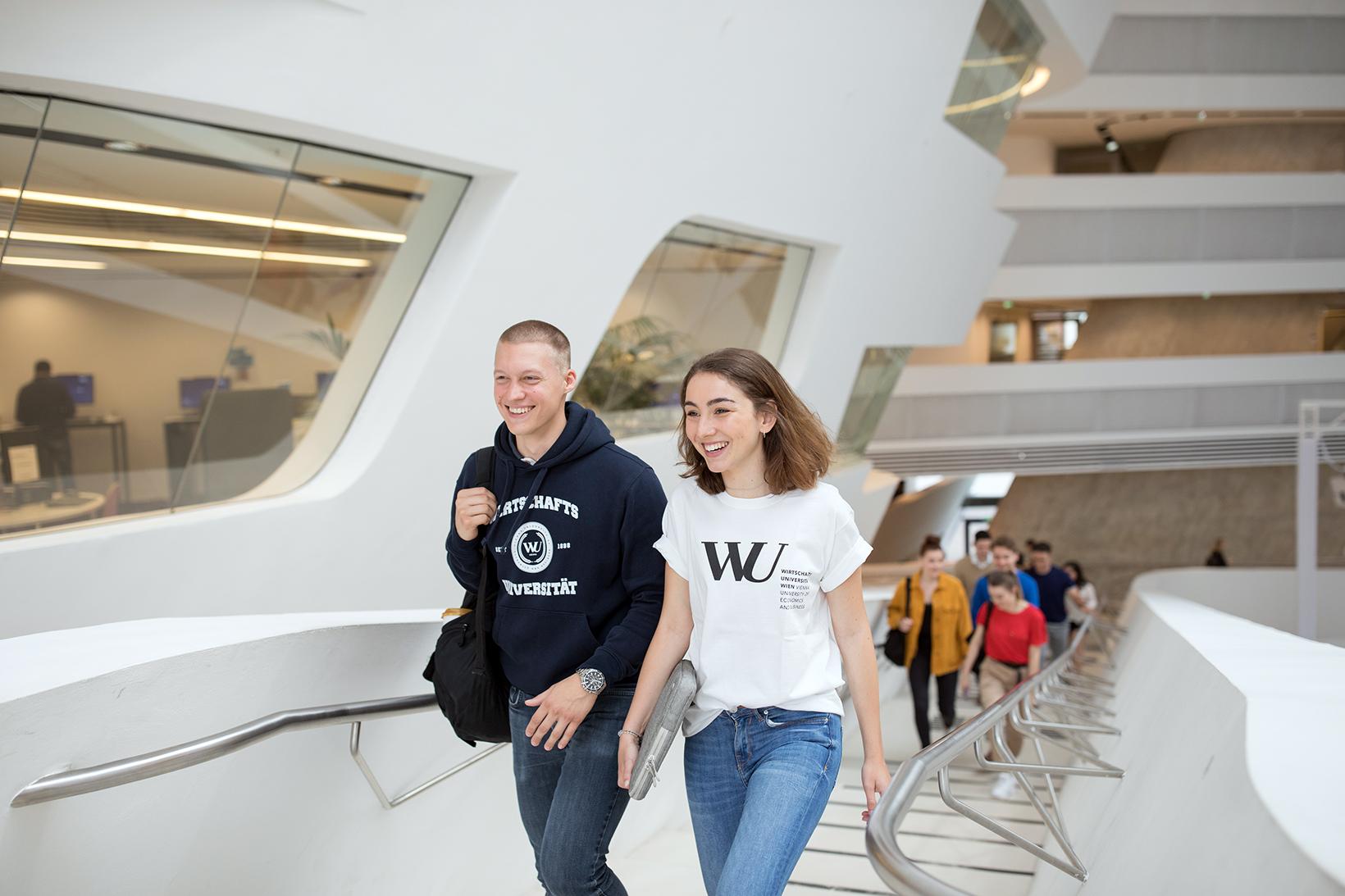 Studierende gehen in der Bibliothek eine Treppe hinauf